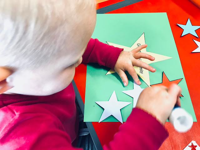 A toddler sticking paper stars on to card with pritt stick