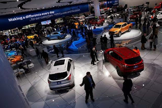 Visitors look at cars in the Ford booth at the North American International Auto Show in Detroit, Michigan, U.S. January 15, 2018. (Credit: Reuters/Jonathan Ernst) Click to Enlarge.
