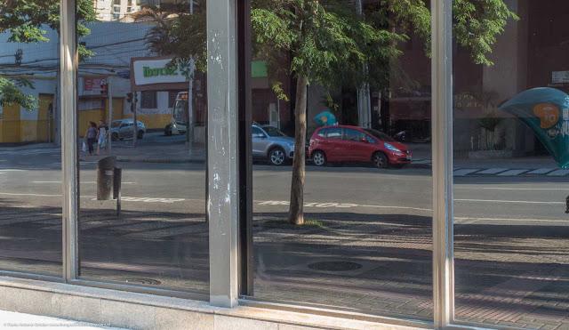 Rua refletida no vidro de um edifício