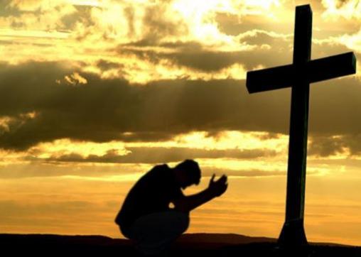 Orang kristen berdoa di depan salib