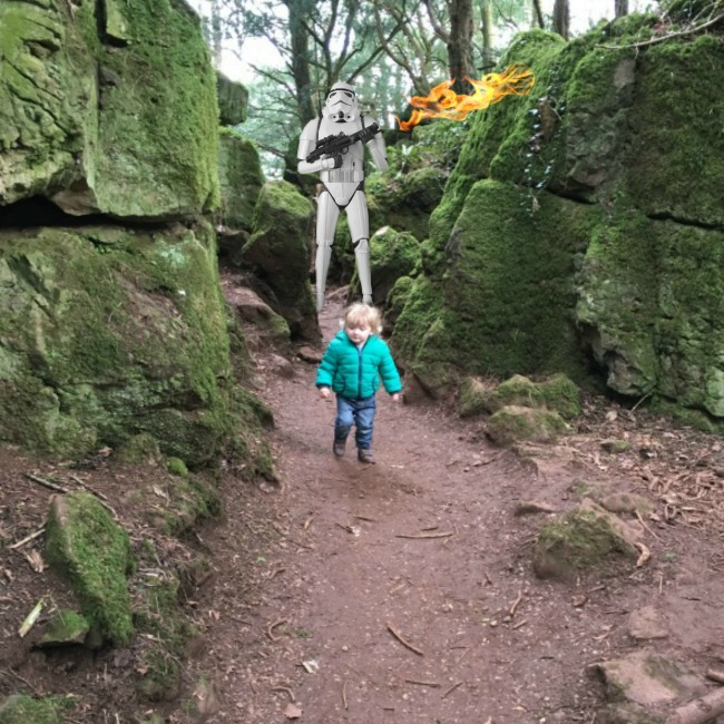 picture-of-toddler-on-narrow-path-between-rocks-with-stormtrooper-holding-flaming-gun-behind