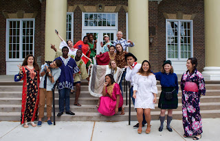 students are standing on a the steps in front of bartlett, wearing traditional clothing from many countries
