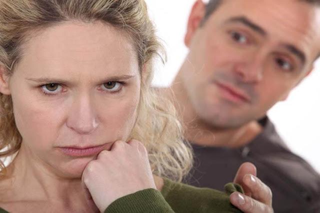 mujer llorando mientras su marido trata de arreglar la relación de pareja