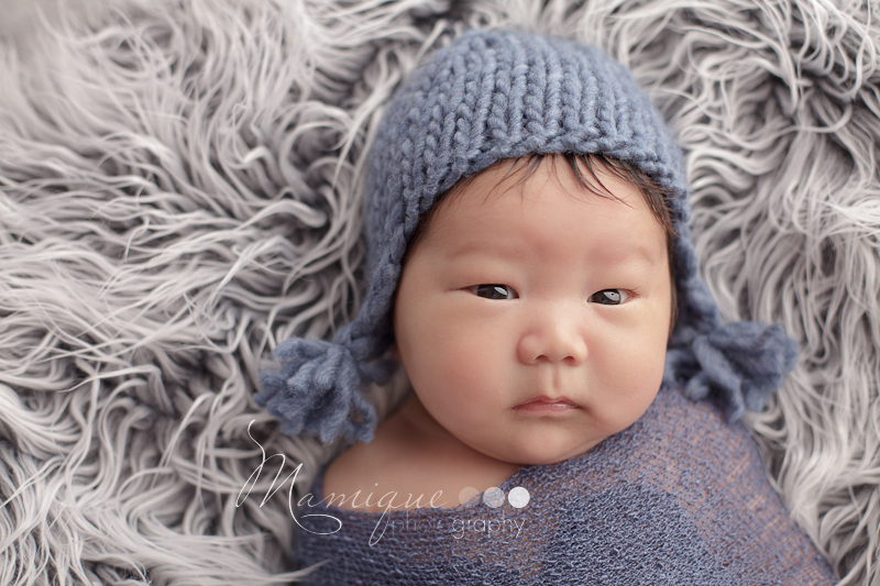 adorable asian boy with big eyes and a blue ear flap hat