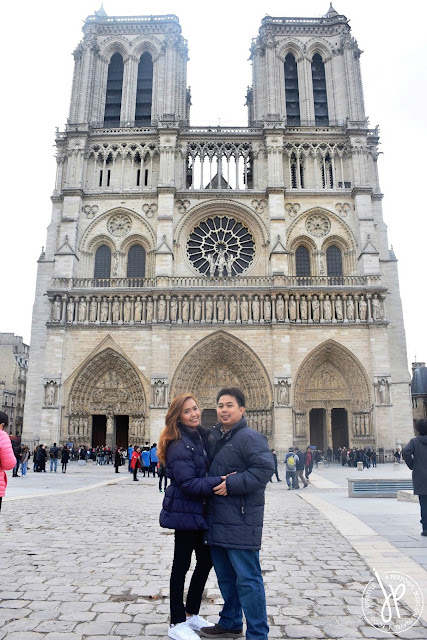 couple posing in front of the church