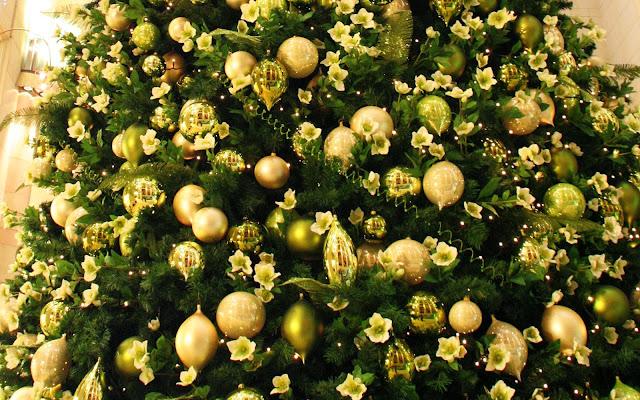 Afbeelding met gele kerstballen en bloemen in de kerstboom