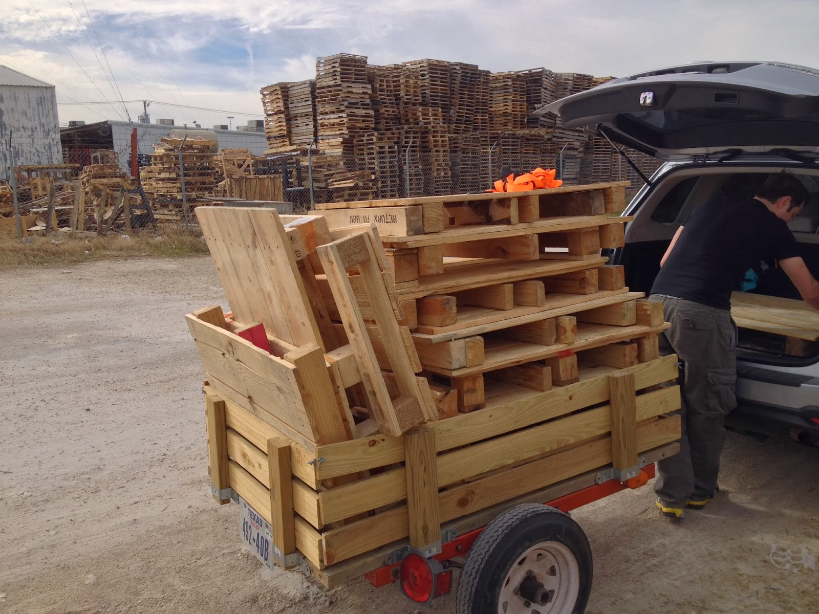 small trailer loaded with pallets and a man standing next to it