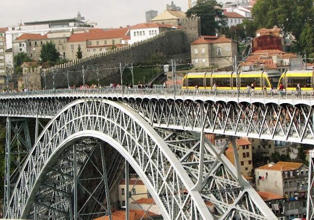 Metro e pessoas passando na Ponte Luiz I no Porto