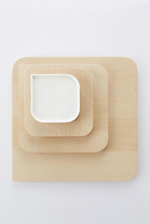 Mehrere Untersetzer aus hellem Holz sind übereinander gestapelt. Darauf stehen weiße Tassen. Designstudio Fou de Feu