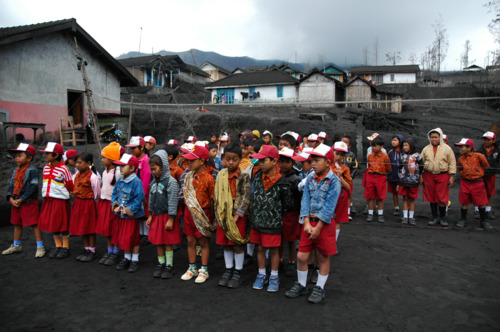 anak-anak berkumpul dengan latar bromo yang erupsi