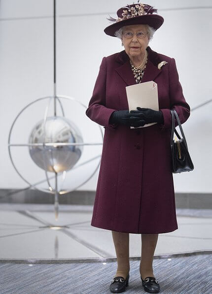 Queen Elizabeth II visited the headquarters of MI5 at Thames House in London. burgundy coat, gold brooch, floral dress