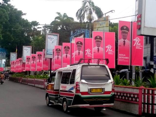 Sebuah angkutan kota melintas di sebelah barisan baliho penyambutan Dirgahayu RI Ke-72, Jalan Sudirman, sudut Lapangan H Adam Malik, Pematangsiantar, Rabu 9/8/2017