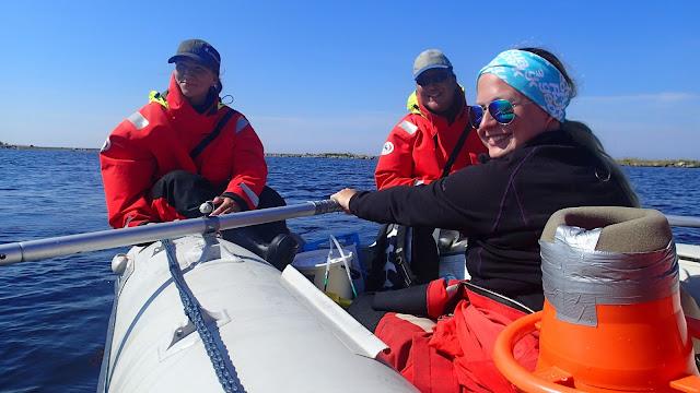 Kolme henkeä kumiveneessä, yksi soutaa