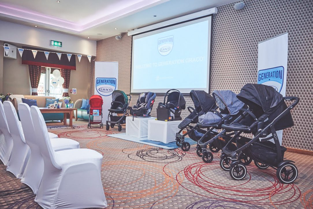 conference room set up with white chairs and Graco pushchairs and car seats on display