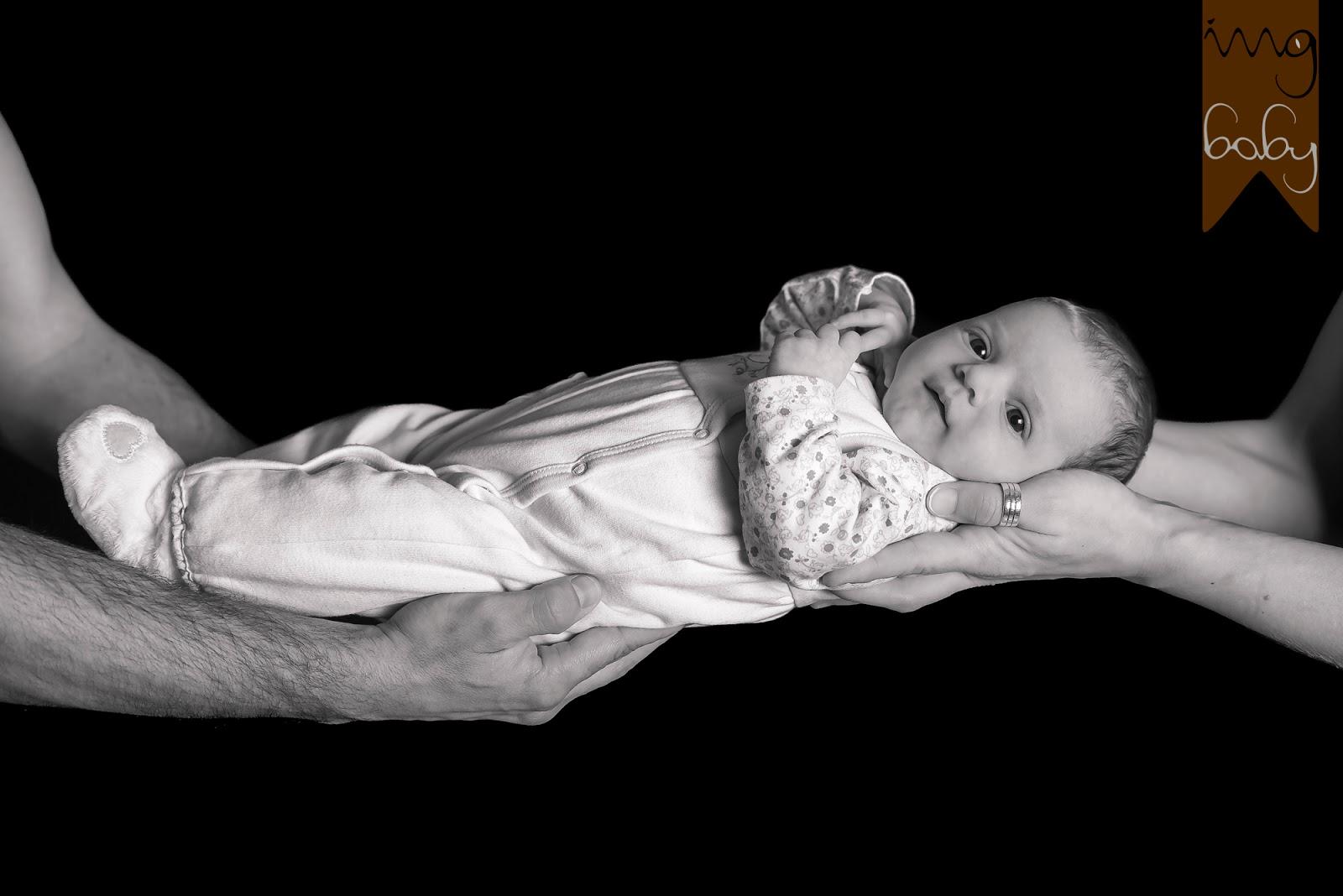 bebé sostenido entre las manos de sus padres