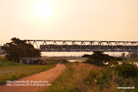 夕陽浴びて鉄橋を走る電車写真