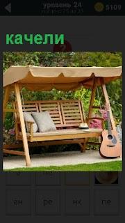 На даче установлены качели с тентом на верху, лежат подушки и оставленная кем то гитара