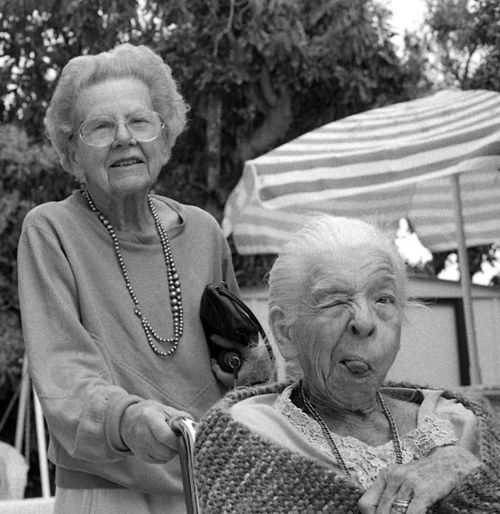 Black and white photo of an old woman, pushing her friend in a wheelchair. Friend winks and sticks her tongue out