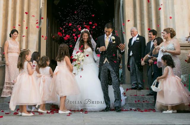 Novios saliendo de la iglesia con arroz y petalos de rosa - ideas blog Odilia Bridal