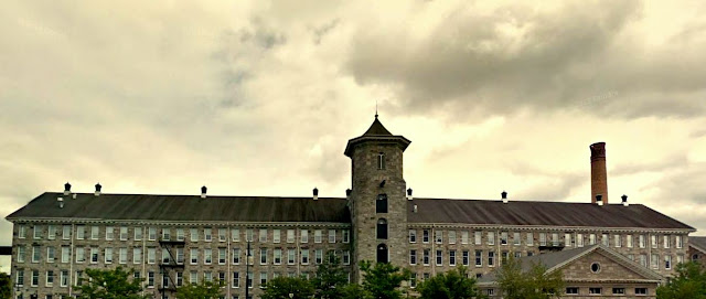 gray stone mill against gray sky, hoistway tower center