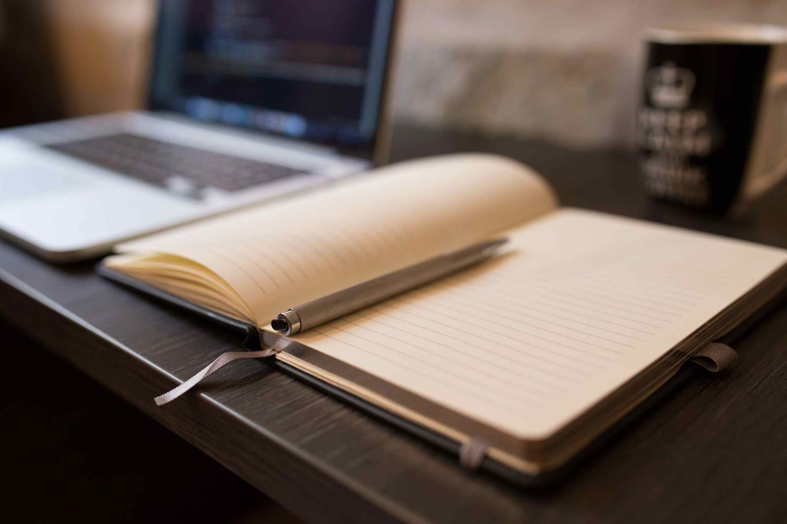 Photo of a notebook and pen with a laptop in the background