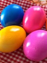 Quattro uova colorate (giallo, blu, fucsia e rosa) su tovaglietta a quadri bianca e rossa.