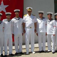 Türk bayrağı önünde bahriyeli deniz subayı ve askerlerin bir fotoğrafı