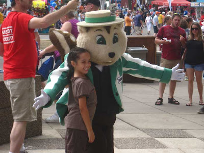 Mascot of a brown striped gopher with a green and white striped jacket and a hat