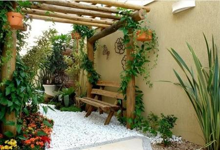 jardim com pergolado e banco rústicos, jardim seco com seixo branco como cobertura e muitas plantas em vasos e suspensas