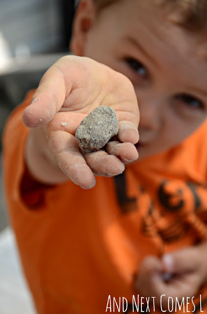 Toddler holding up a small ball of sand play dough