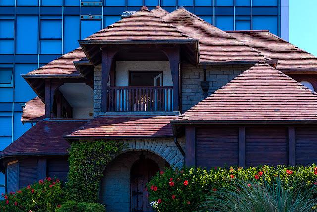 Casa con techos en triangulos y hermoso jardin florido.