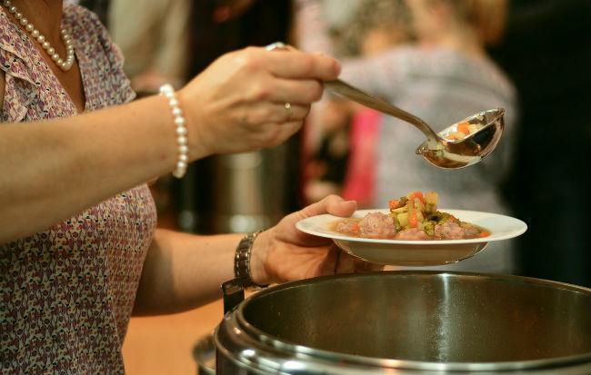 Donna anziana che riempie il piatto di cibo