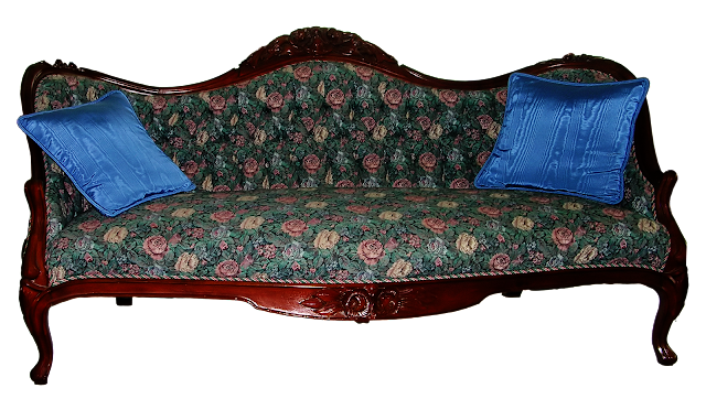 A mid to late Victorian sofa with a carved walnut frame and covered in reproduction fabric with pink and yellow roses.