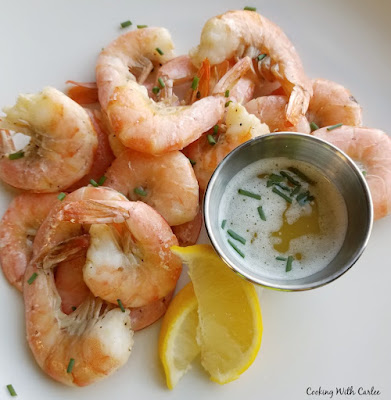looking down on dinner plate of key lime roasted shrimp with dipping sauce and lemons
