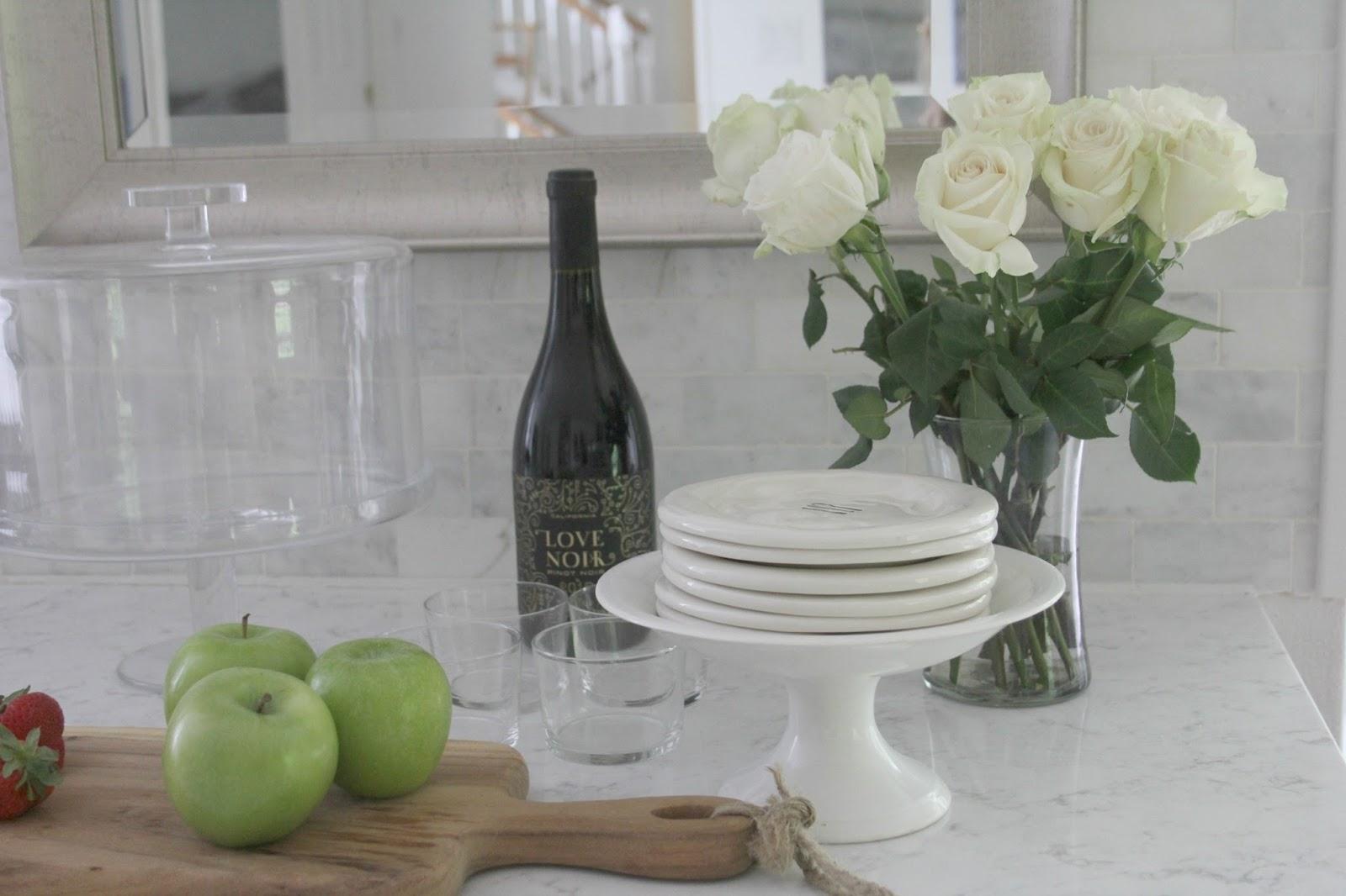 Marble subway tile, quartz countertop, and white roses in modern farmhouse kitchen