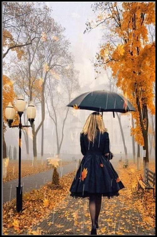 Uma jovem protegendo-se da neve que cai, com uma sombrinha, caminha entre as árvores cujas folhas coloridas espalham-se no chão.