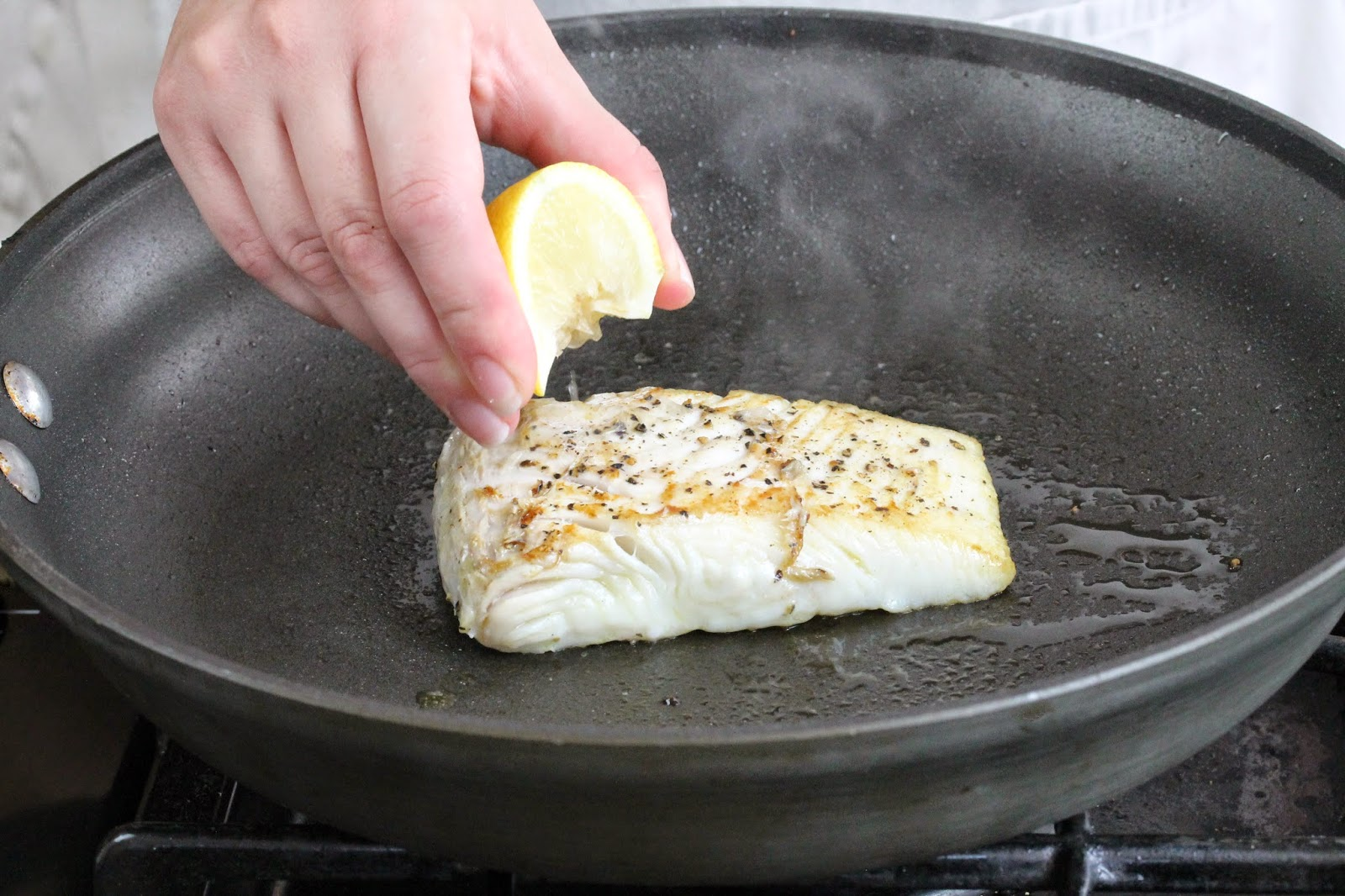 Rachel squeezes juice from a fresh lemon wedge onto the fish filet