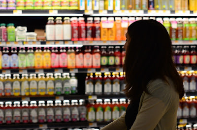 woman looks at juice bottles in grocery store