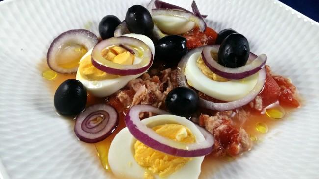 Una ensalada de tomate de bote, atún, cebolla y huevo