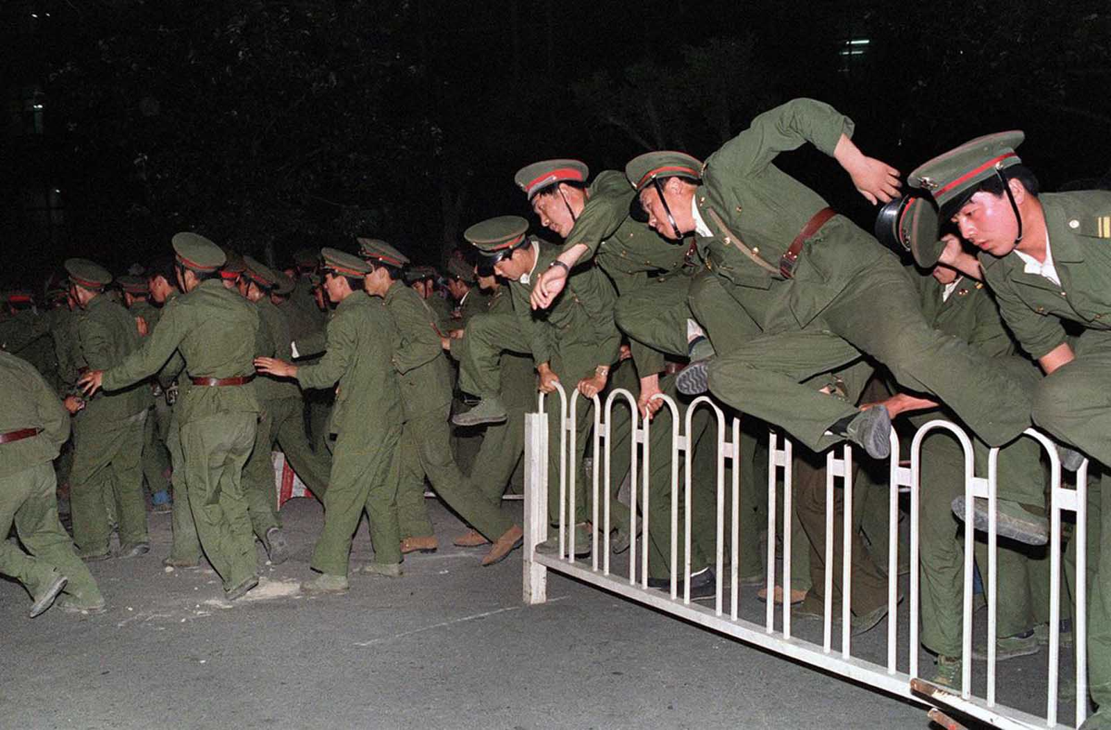 People's Liberation Army (PLA) soldiers leap over a barrier on Tiananmen Square on June 4, 1989, during heavy clashes with people and dissident students. The PLA was reportedly under orders to clear the square by 6:00 am, with no exceptions.