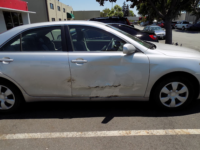 Camry with big dents on doors before collision repair at Almost Everything Auto Body.