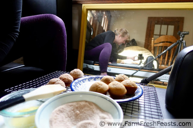 a picture of behind the scenes while photographing the muffins, with the plate of muffins on a pilates machine, camera and tripod visible in the mirror