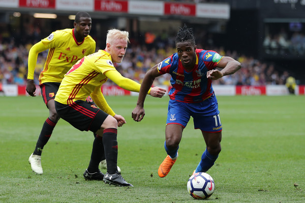 Wilfried Zaha of Crystal Palace runs with the ball away from presure by Will Hughes of Watford during the Premier League match between Watford and Crystal Palace at Vicarage Road on April 21, 2018 in Watford, England.