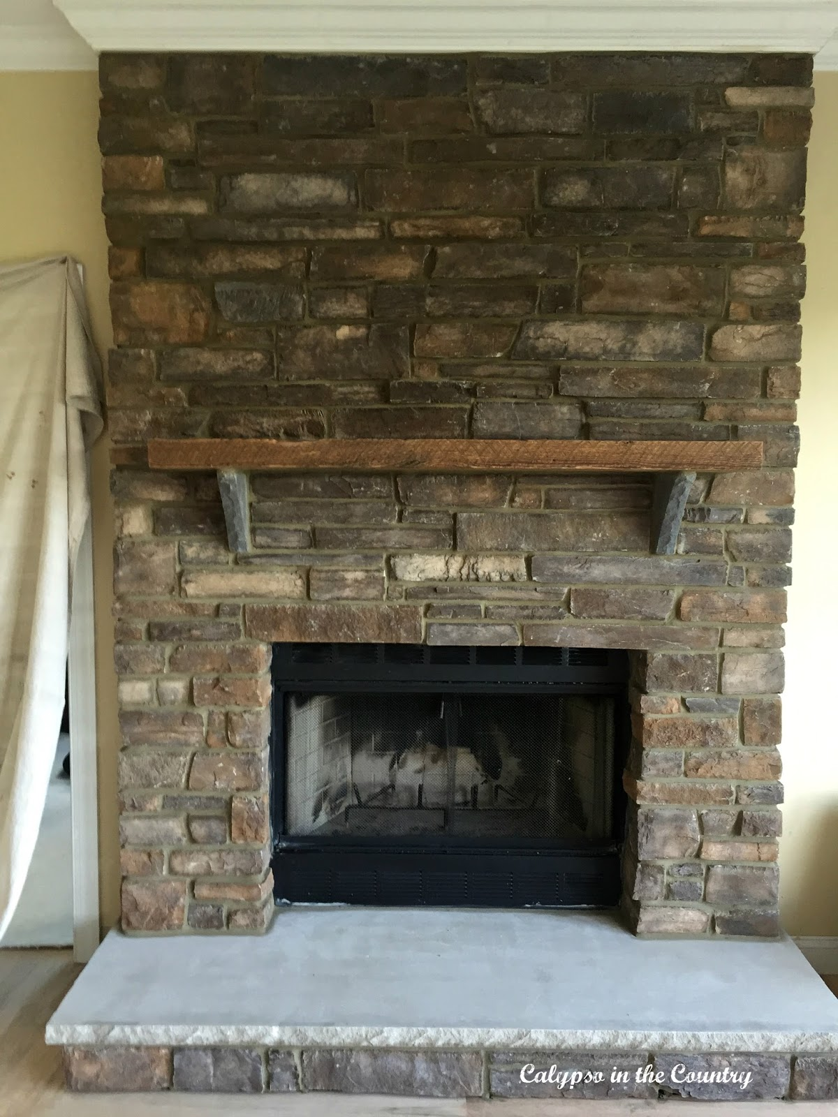 Before and After stone fireplace with rustic mantel - final reveal