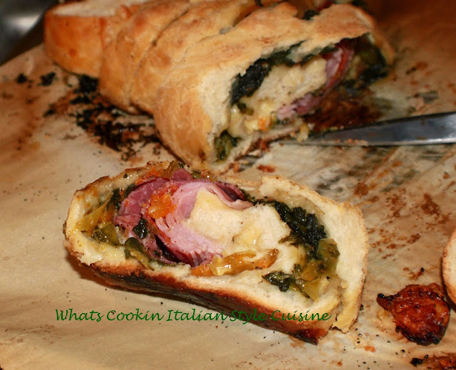 this is a pizza dough with a filling of Antipasto ingredients. there are tomatoes, escarole, salami, mortadella, hot capicola and imported Italian cheeses in this roll baked and this is sliced to show what the filling looks like inside