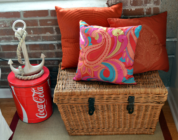 Straw basket orange pillows coca cola tin anchor decor