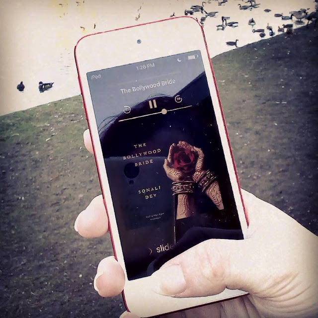 A white hand holds a red-bordered iPod up against a pond filled with Canada Geese. The screen holds the black cover of The Bollywood Bride, which features two henna-decorated hands cupping a lush red flower.