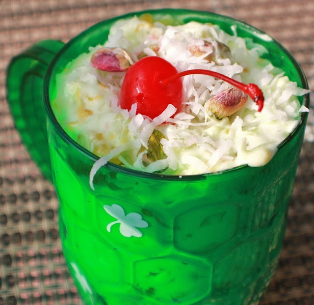 Ambrosia Salad that is green in a St Patrick's Day plastic cup with shamrocks on it