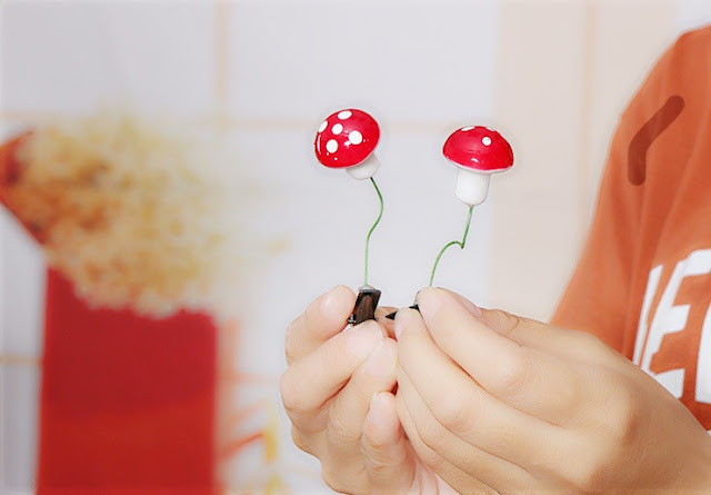 Hands holding up mushroom hair pins