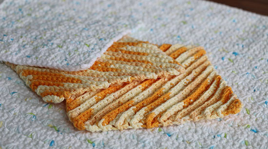 Two bright orange crocheted cotton Diagonal Dishcloths on an Alex Bath Mat with another cloth made from the Alex pattern